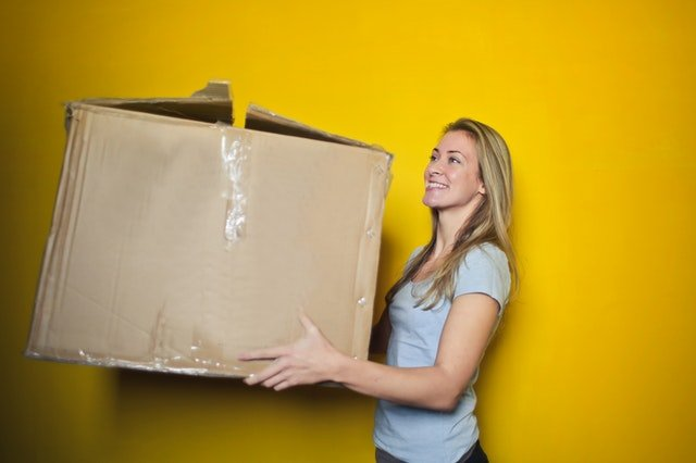 photo of woman carrying a box by Andrea Piacquadio