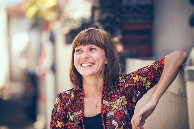 photo of woman smiling by Artem Beliaikin